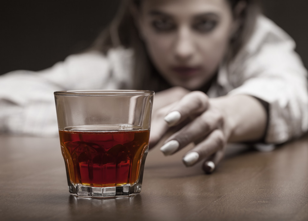 woman reaching for a glass of alcohol