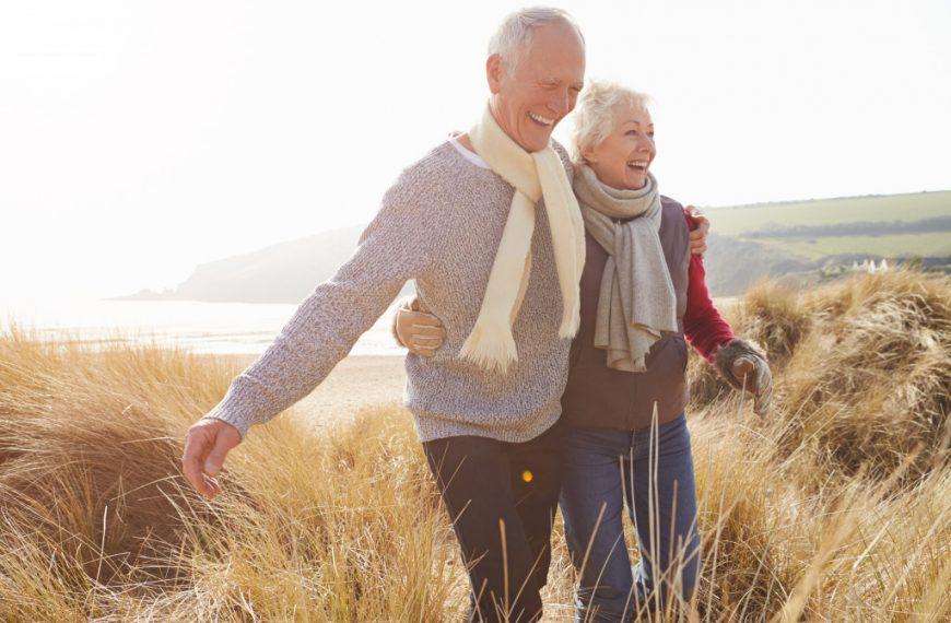 senior couple walking through a field