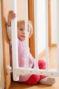 baby beside a door fence