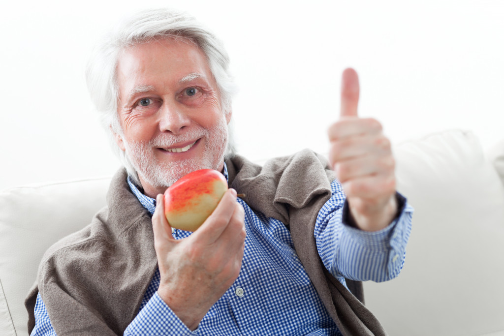 old man holding a fruit